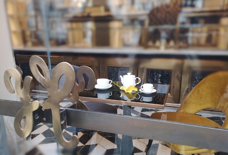 Uno sguardo sul Bar Hungaria attraverso l'ingresso vetrato con la maniglia in acciaio. All'interno due tazze da tè e una teiera sul tavolino