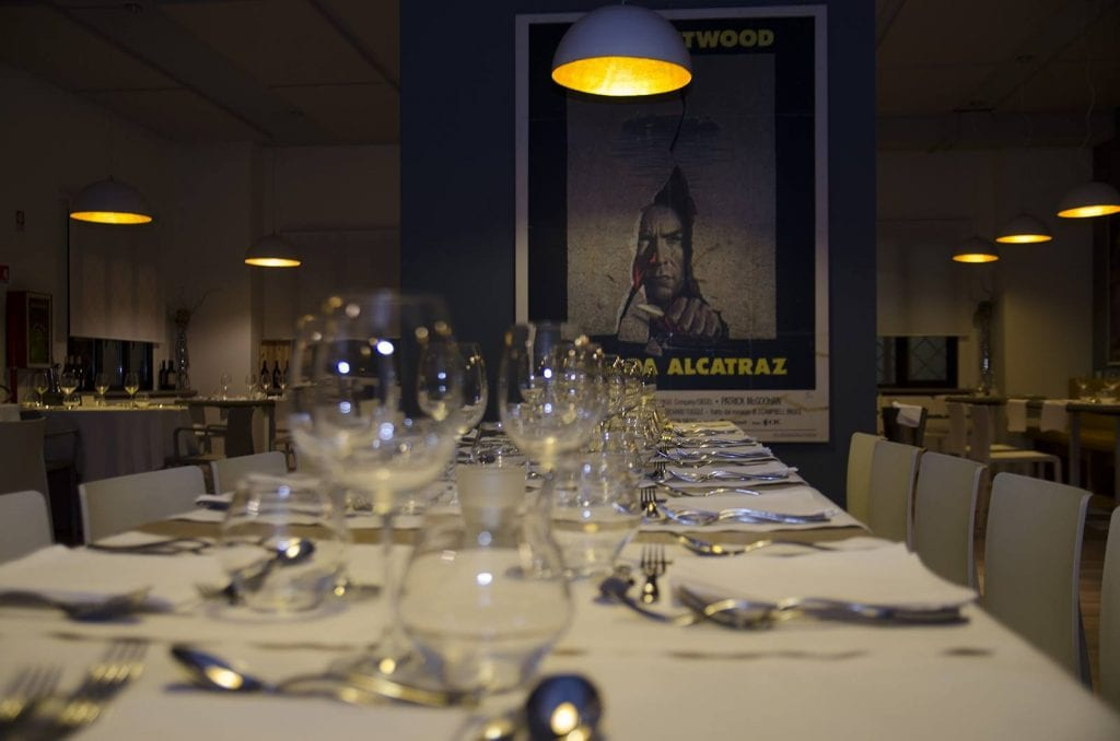 Tavolo apparecchiato con locandina del film fuga da Alcatraz sullo sfondo