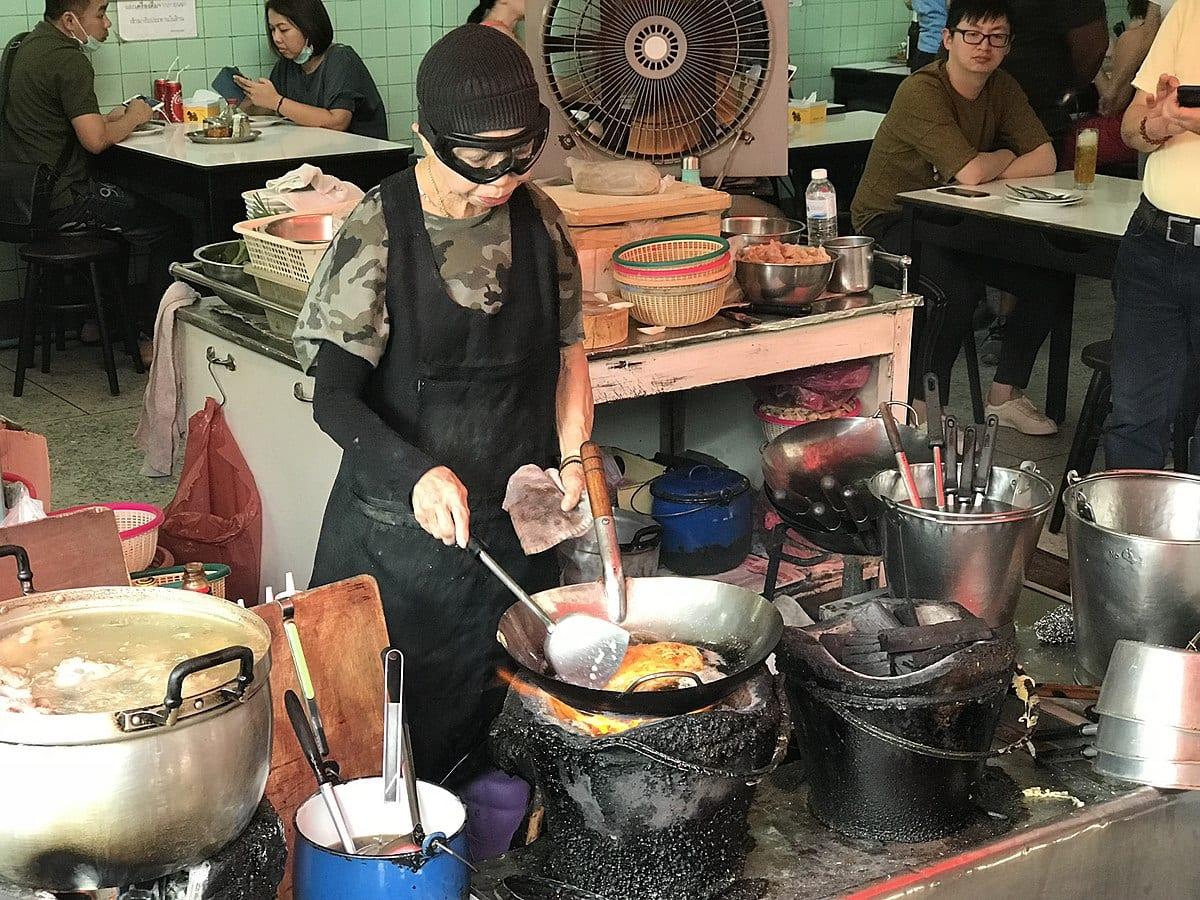 Jay Fai al lavoro con la maschera davanti alla padella delle omelette