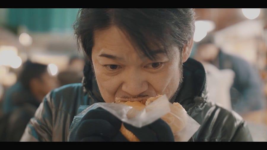 Kotaro Noda addenta una specialità di street food