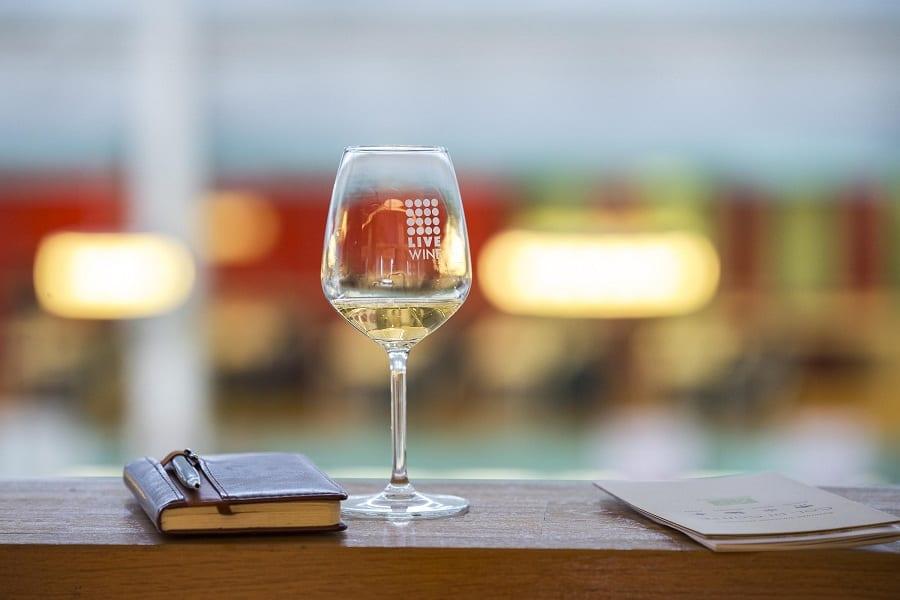 Un calice di vino bianco su una mensola, con agenda per prendere appunti