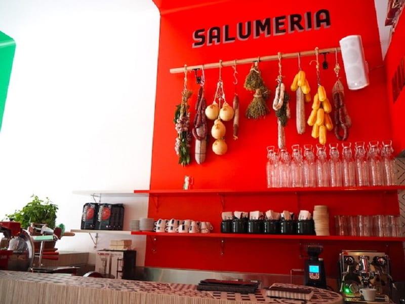 la parete rossa della slaumeria Mallozzi, con formaggi e salumi appesi