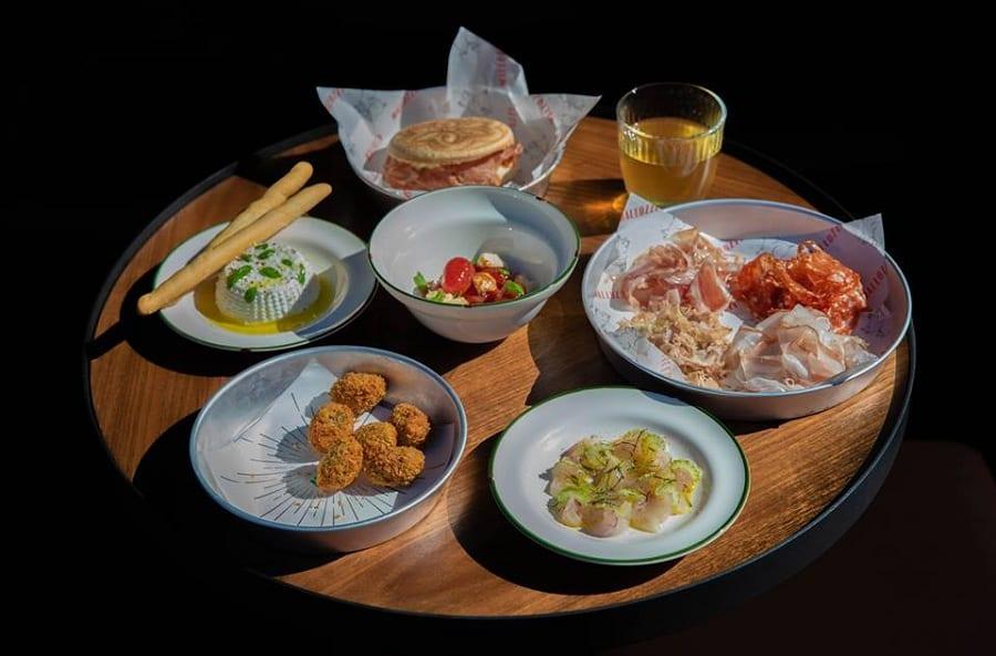 Sfizi di cucina italiana sulla tavola di Mallozzi: salumi, olive ascolane, ricotta, tigella con mortadella, insalata caprese