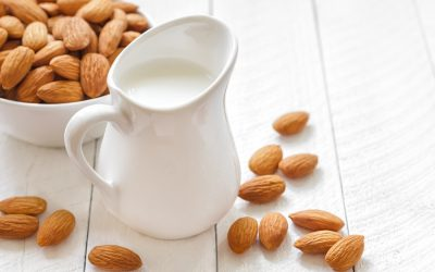latte di mandorla in bricco bianco con mandorle e ciotola di mandorle su tavolo a doghe in legno bianco