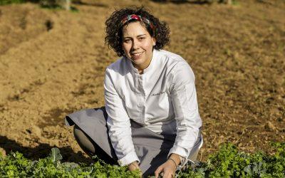 Ritratto di Martina Caruso nei campi, con la fascia nei capelli e la divisa da chef