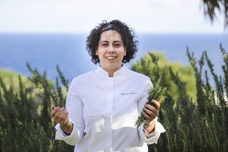 Martina Caruso tra cespugli di rosmarino e sullo sfondo il mare di Salina