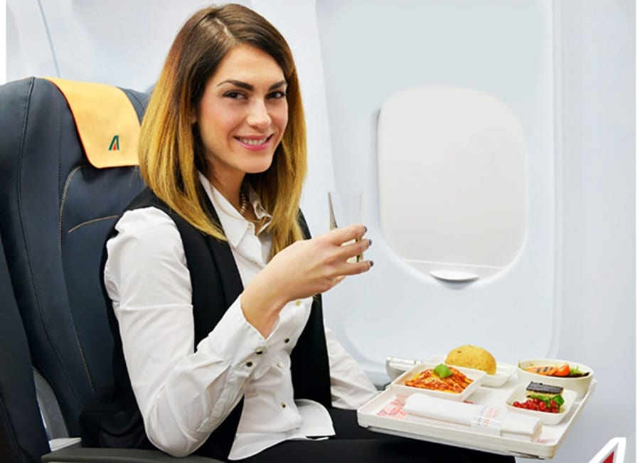 Una hostess di alitalia mangia seduta a bordo dell'aereo