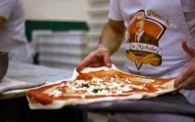 Un pizzaiolo condisce la pizza Margherita prima di infornarla
