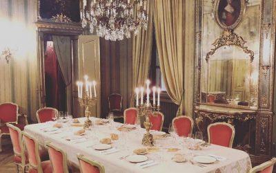 La sala di Palazzo Saluzzo con la tavola apparecchiata, con candelabri, stoviglie di porcellana, sedie in velluto rosso, un lampadario a gocce e tendaggi oro sullo sfondo