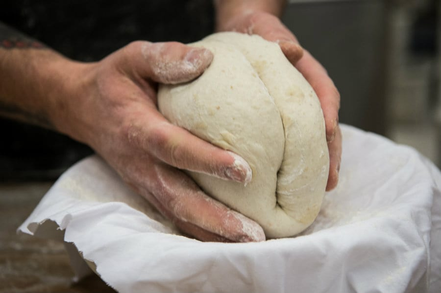 Mani che impastano il pane. Foto di Francesco Vignali
