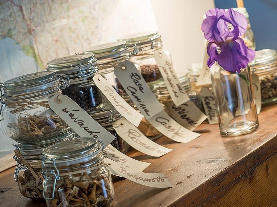 Le erbe aromatiche dentro barattoli in vetro con etichette scritte a meno, su una mensola in legno e un fiore d'iris viola