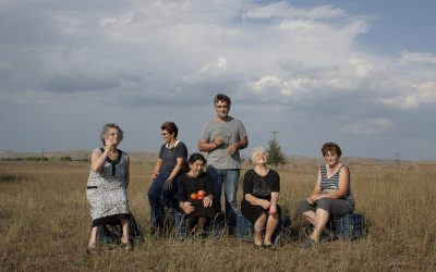 Cinque donne e un uomo in un campo con i pomodori in mano
