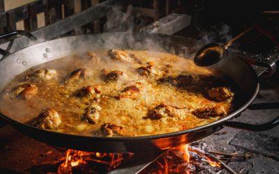 Una paella con riso in cottura su fuoco vivo