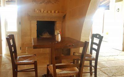 La sala di Roots a Scorrano, pareti in pietra, tavolo in legno nudo, camino sullo sfondo