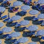Ombrelloni bianchi e blu aperti in spiaggia, visti dall'alto
