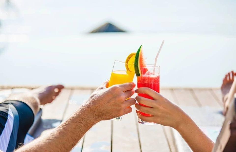 Brindisi in riva al mare, con due cocktail tropicali