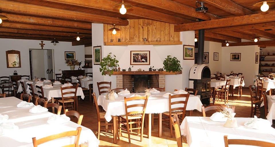 La sala del bioagriturismo Valle Scannese, con tavoli e boiserie in legno e camino