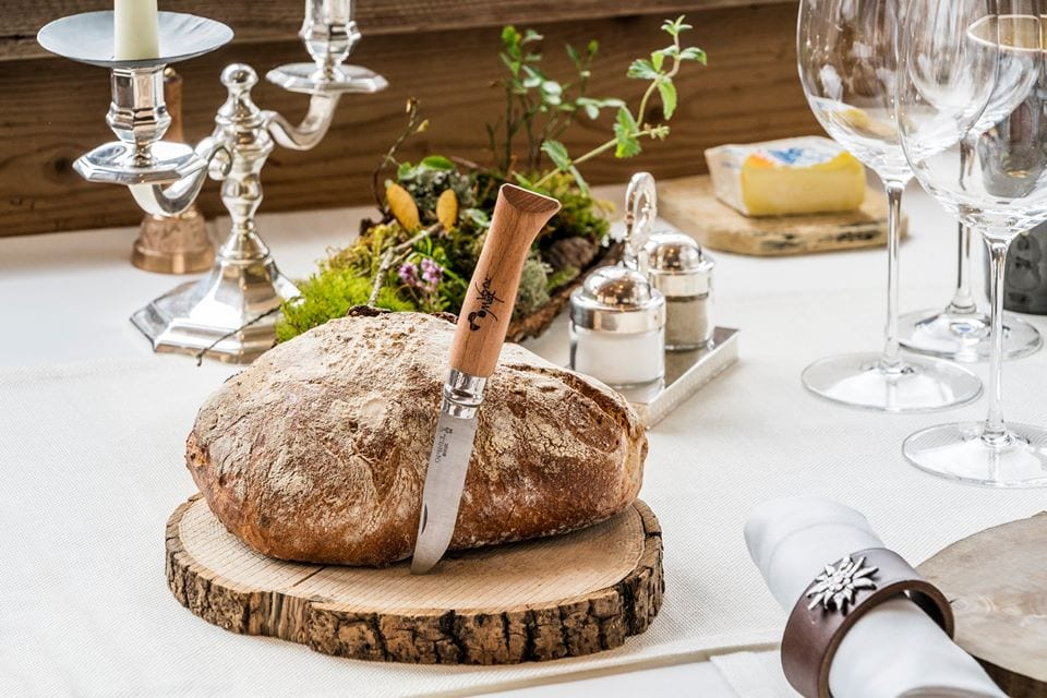 La tavola di Marc Veyrat a La Maison de Bois, con pane sul tagliere in legno e coltello firmato dallo chef