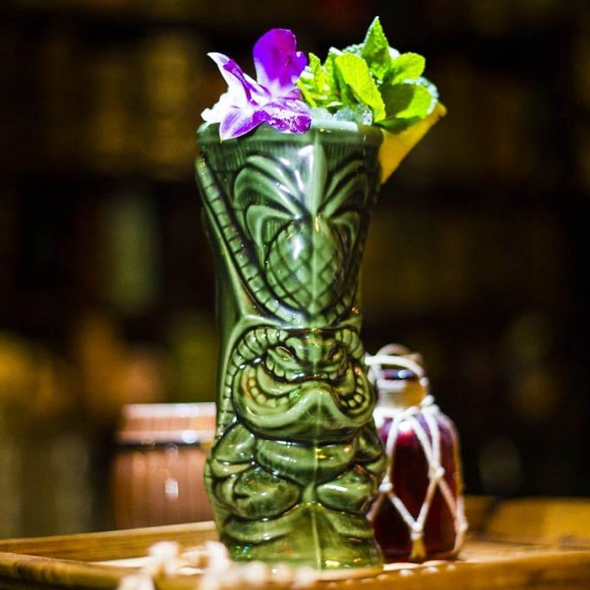 Un tiki cocktail in tiki mug verde decorata con fiori viola e menta