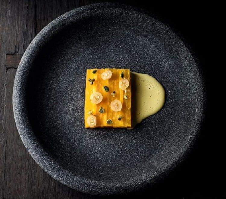 Un piatto del menu di Under, fotografato dall'alto, su fondo nero