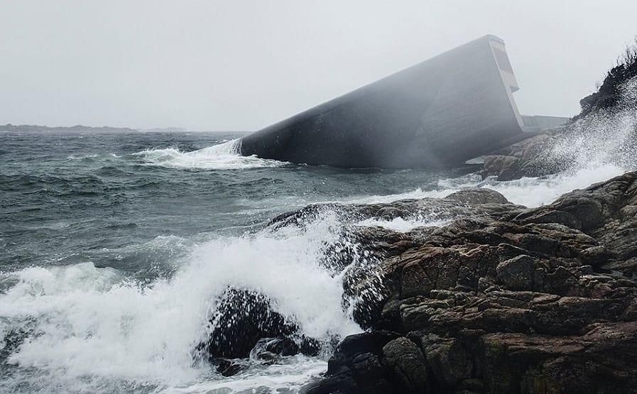 Il monolite di Under che emerge dalle onde sulla scogliere norvegese di Baly