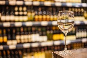 un calice di vino bianco e sullo sfondo gli scaffali