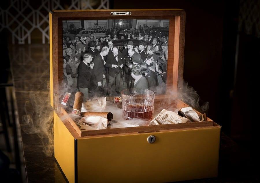 Un cocktail dentro una scatola in legno aperta con foto d'epoca in bianco e nero