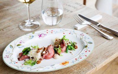 I ravioli di girello del ristorante Vite, nella mise en place con piatto decorato a fiori, tavolo di legno nudo, calice di vino bianco
