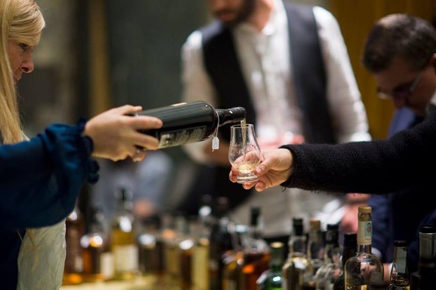 L'assaggio di un whisky, versato dalla bottiglia nel bicchiere
