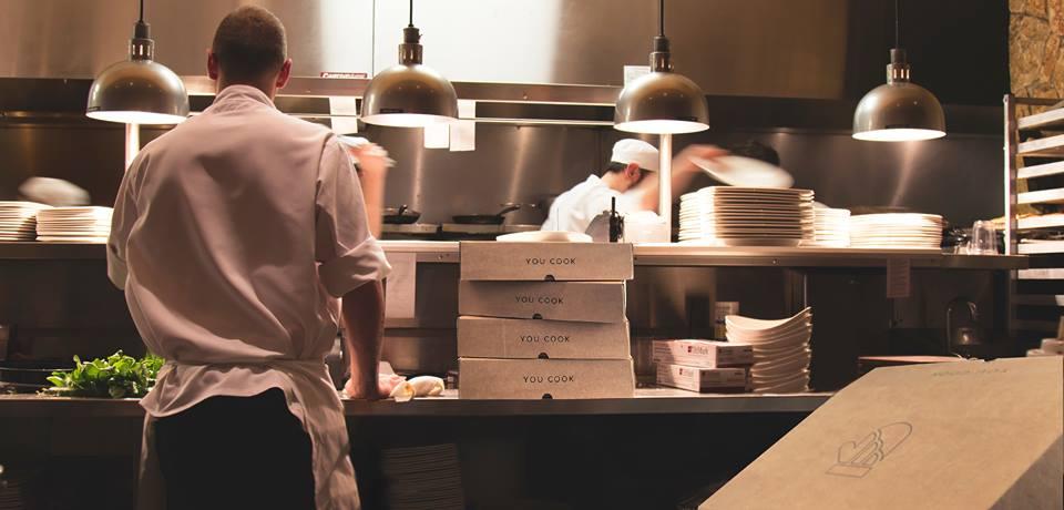 Una cucina professionale, con il cuoco di spalle e le scatole di You Cook per il food delivery
